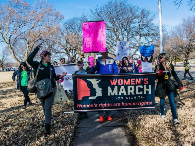 USA people marching holding banner women's march femlens