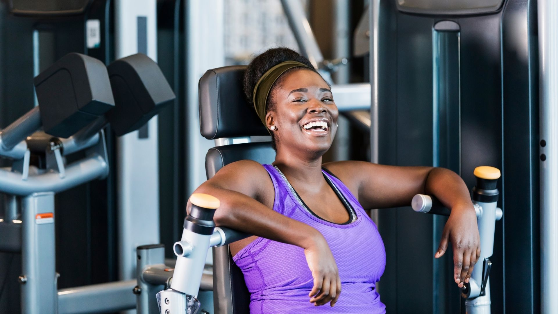 woman smiling while working out at the gym