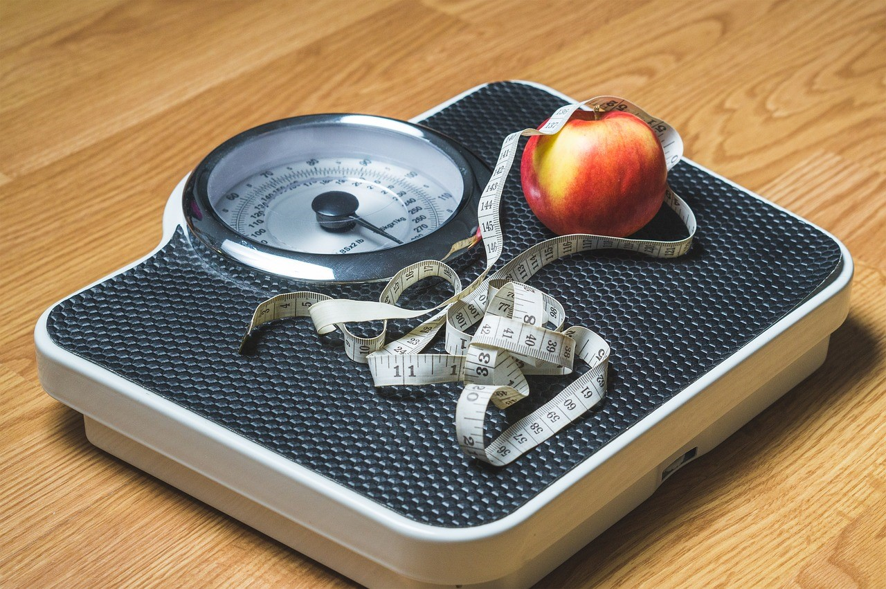 scale measuring tape and apple