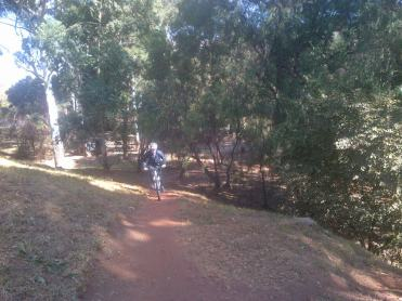 Wes cycling up to the top of the biggest hill at Emmarentia