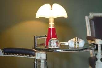Une paire de fauteuils Louis XVI signés Lebas (Damidot Antiquités), recouverts de cuir, entourent une table d'Eileen Gray 1927 en chrome et verre (Conran Shop Paris). Lampe Mini Pipistrello de Gae Aulenti 1965 (Le Bon Marché Paris) et voiture en porcelaine d'un artiste viennois.