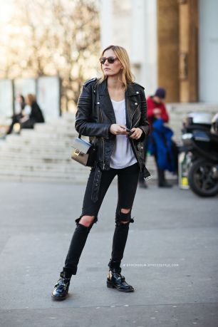 model wearing a leather jacket and black ripped jeans