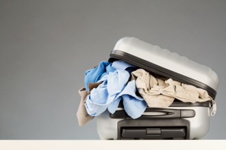 A suitcase over-packed with various casual clothes lying on a white surface with a gray background.