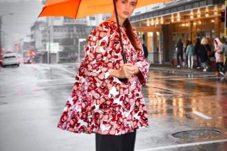 woman stands ina rainy wellington street holding a reflective orange umbrella and wearing a reflective lumen coat