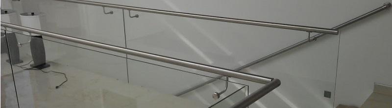 Barandal de cristal, sistema adosado, con pasamanos de acero inoxidable.