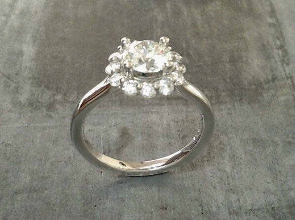classic vintage style white gold engagement ring with round cut diamond in a halo setting