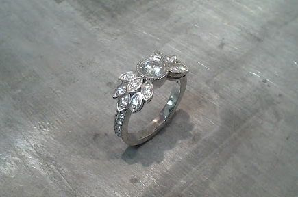custom designed white gold engagement ring by sean ferguson with round cut diamond and diamond leaf accents side view