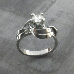 custom designed swirled leaves white gold band with princess cut diamond in cathedral setting