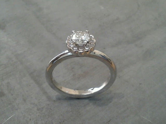 minimalist custom designed band with a princess cut diamond in a flower halo setting