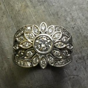intricate thick custom engraved band with round center diamond and surrounding marquise diamonds in a flower setting