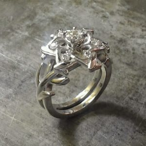 unique custom designed engagement ring with circle cut diamond and star flower diamond setting with leaf band side view