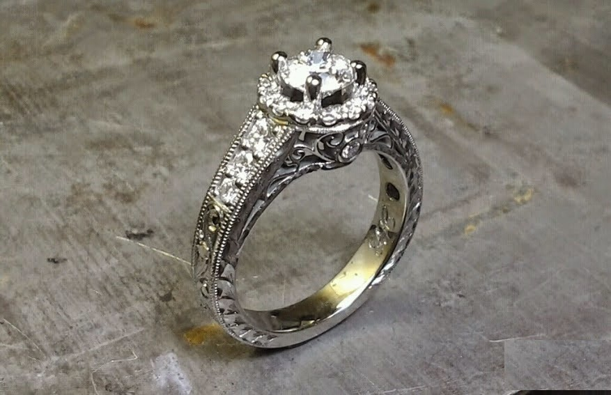 intriciate engagement ring band engraved with filigree and a princess cut diamond in a halo setting side view