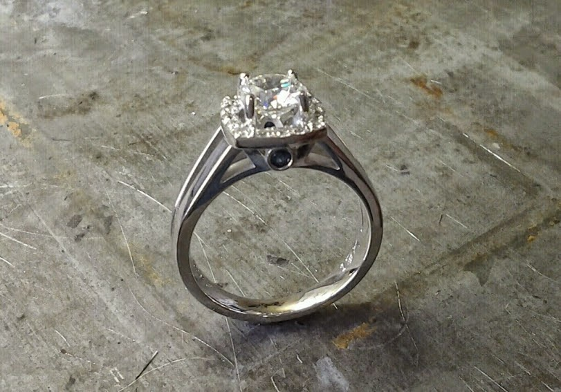 simple split white gold band with large round diamond and diamond halo setting and black accent diamond