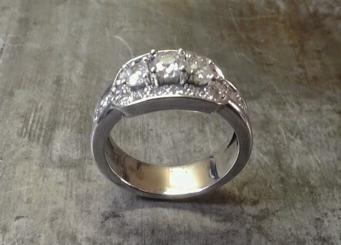 custom designed white gold engagement ring with three large diamonds surrounded by smaller ones side view