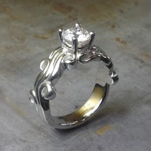 custom designed swirled band with princess cut center diamond