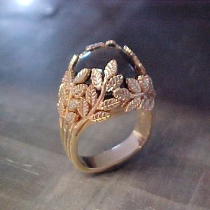 custom ring with leaf engraving holding center stone
