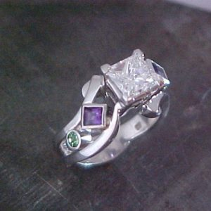 custom ring with large center diamond with purple and green sapphires in band