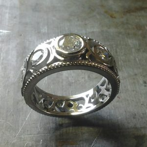 custom swirled band with round bezel set diamonds top view