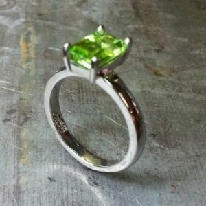 slim band ring with large green sapphire
