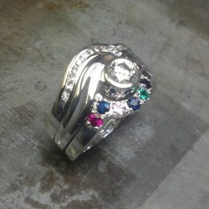 custom family ring with multiple birthsones and diamonds side view