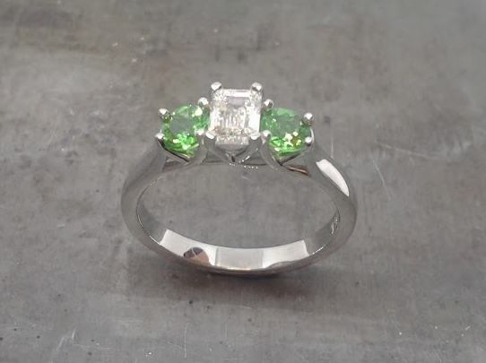 Emerald cut diamond and Tsavorite engagement ring
