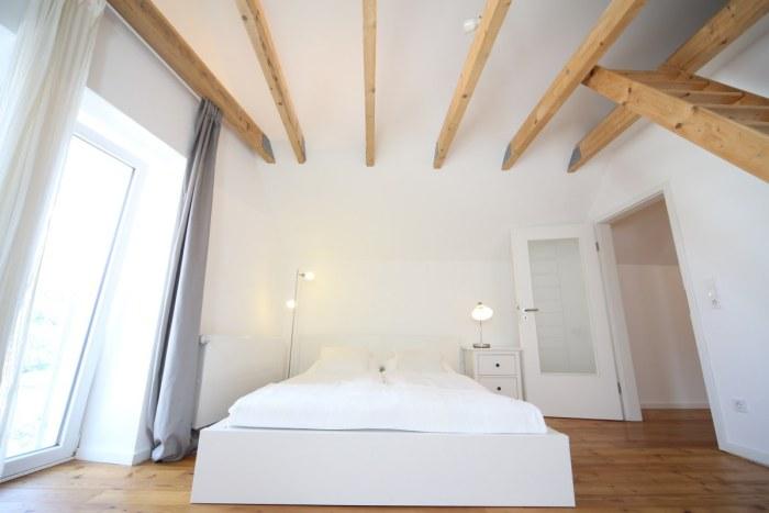 """Breites Doppelbett und Holzbalkenkonstruktion im Schlafzimmer des Mainzer Ferienhauses """"Hofhaus""""."""