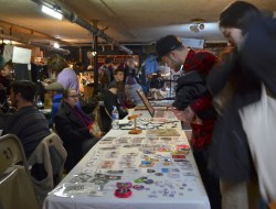 Customers looking at the different items for sell on a table inside the market.