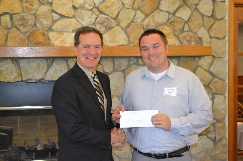Rayonier Advanced Materials Fernandina Plant General Manager C.A. McDonald presents a grant to Tom Christenson of the Nassau Humane Society.