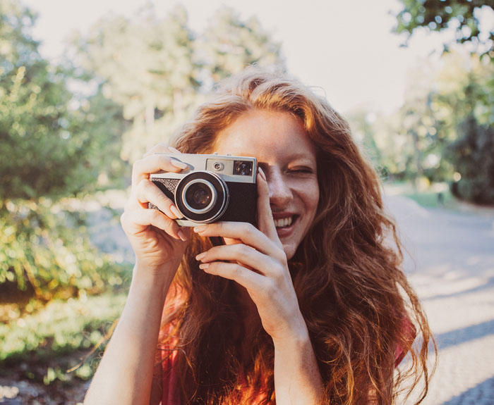 Smiling Ginger Woman Taking a Photo
