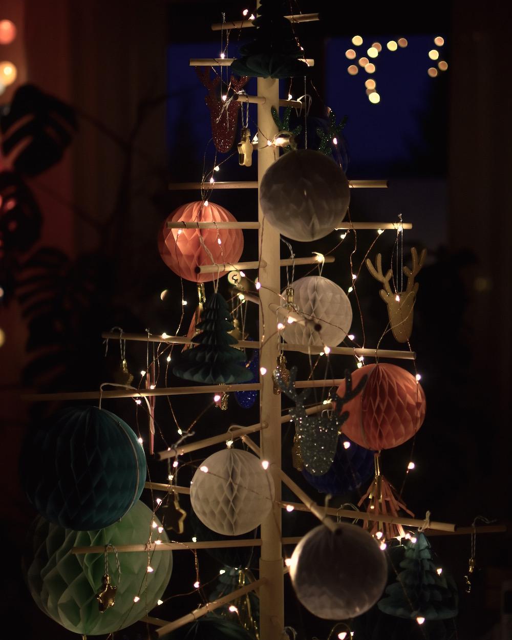 Nachhaltiger Weihnachtsbaum aus Holz geschmückt mit Wabenbällen