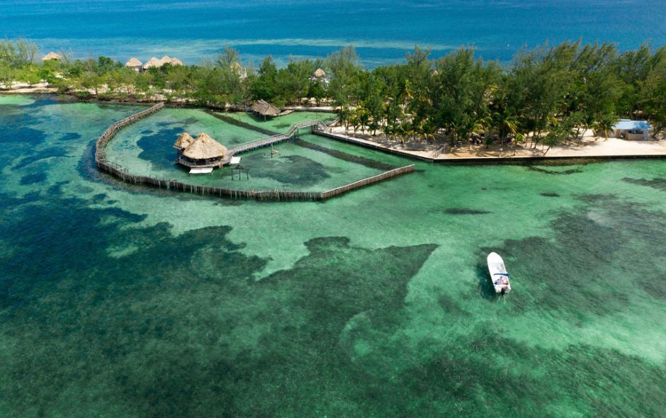 Aerial photo of Thatch Caye island in Belize with blue water and overwater bungalows
