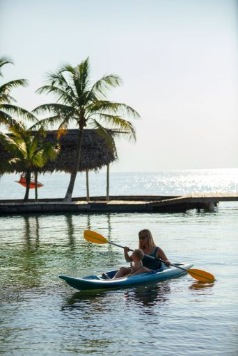 Mother and baby kayaking in calm ocean off Thatch Caye island in Belize