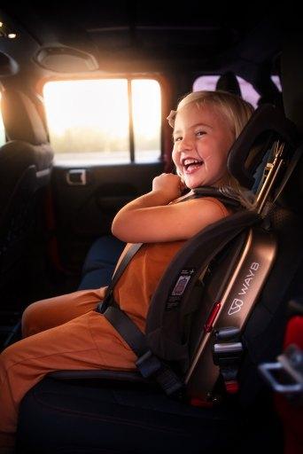 Toddler girl smiling and sitting in WAYB Pico Travel Car Seat