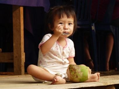 Das kleine Mädchen in Luang Prabang (Laos) löffelt genussvoll die Kokosnuss leer.