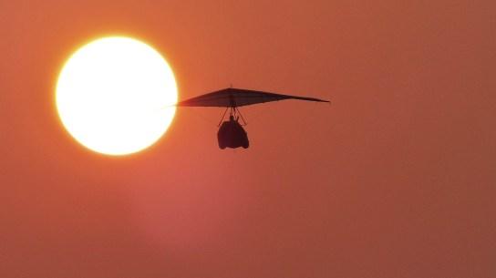 Der Ultralight-Flieger am Strand von Sihanoukville (Kambodscha), der in die Abendsonne fliegt.