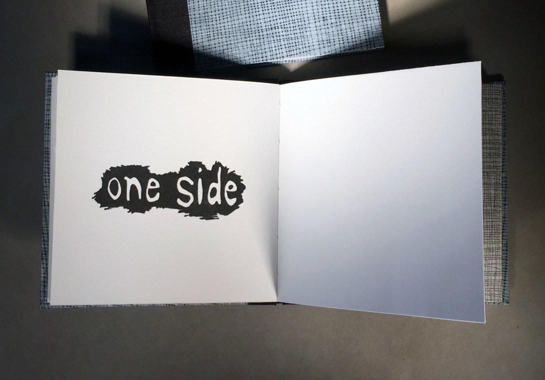 """Interior page of an artist book titled """"1 over 1"""", text says """"one side"""""""