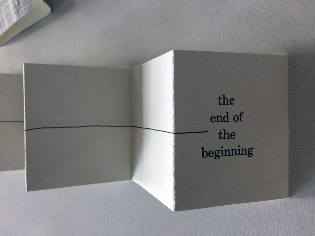 "Wrap and first panel of accordion artist book by Wendy Fernstrum titled ""Omegalpha""; text says ""the end of the beginning"""
