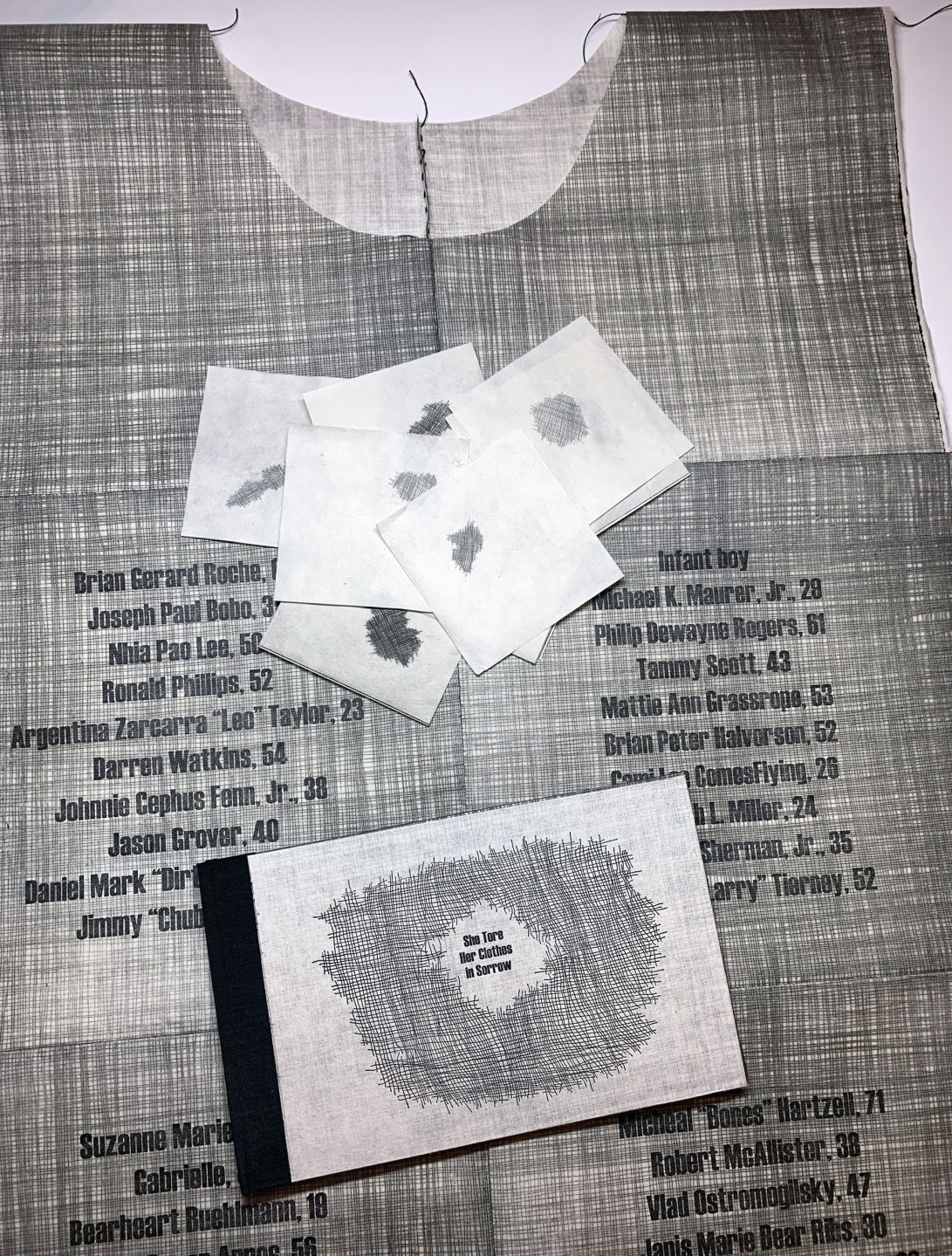 "Image showing the 3 elements of the artist book ""She Tore Her Clothes in Sorrow"": a tunic, torn pieces of cloth, and a bound book"