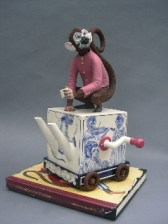 "Red Weldon Sandlin, ""The Hurtea Gurdy Tales: A Nickel for the Monkey"" 2006, ceramic, wood, acrylic paint, 16.5 x 11.5 x 11"", book 1 x 12 x 9""."