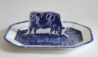 "Paul Scott, ""Scott's Cumbrian Blue(s), Cow in a Meadow No. 2,"" 2015, glaze, decal, gold, c. 1850 feathered-edged pearlware platter, cow: 5 x 8.75 x 2, octagonal platter: 12.5""."