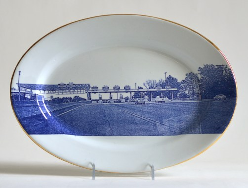 "Paul Scott, ""Scott's Cumbrian Blue(s), American Scenery, (New Jersey) Turnpike No: 4,"" 2015, glaze, decal, gold, Meakin ironstone platter, 10 x 14.25 x 1.5"". Newark Museum Collection."