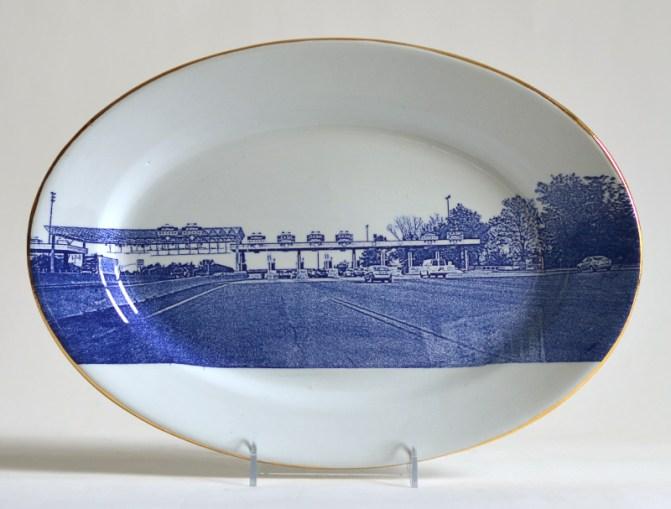 "Paul Scott, ""Scott's Cumbrian Blue(s), American Scenery, (New Jersey) Turnpike No: 4,"" 2015, glaze, decal, gold, Meakin ironstone platter, 10 x 14.25 x 1.5"". Newark Museum Collection."