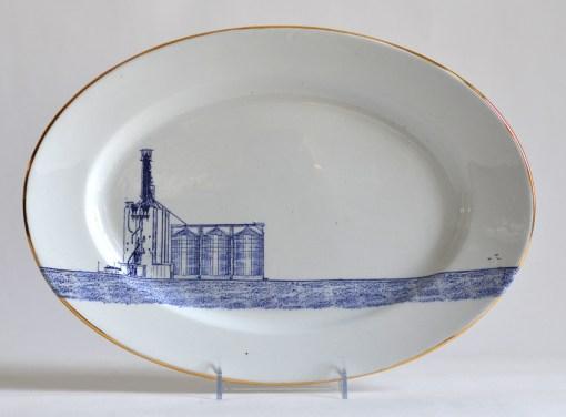"Paul Scott, ""Scott's Cumbrian Blue(s), Grain Silo,"" 2015, glaze, decal, gold, c. 1850 J K Meakin ironstone platter, 10.25 x 15 x 1.75""."