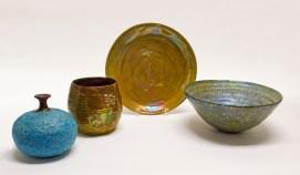 "Beatrice Wood, ""Blue Lava Glaze Vase"" c. 1960, 6 x 7 x 7"". ""Luster Vessel"" c. 1970, stoneware or earthenware, 6 x 6.5 x 6.5"". ""Gold Luster Plate"" c. 1970, 2 x 12.5 x 12.5"". ""Lava Glaze Bowl"" c. 1950-60, 5 x 11.5 x 11.5""."