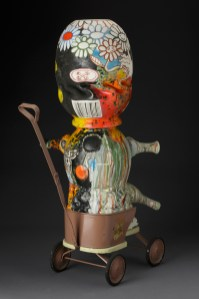 "Michael Lucero, ""Anthropomorphic Baby Form in Stroller (New World Series)"" 1995, glaze, ceramic, carriage, 27 x 12 x 11""."