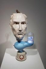 "Sean Erwin, ""Adoration of the Golden Calf"" 2013, polished porcelain, glaze, steel, resin, cast cement, LED lights, glass, flocking, 9 x 10 x 22""."