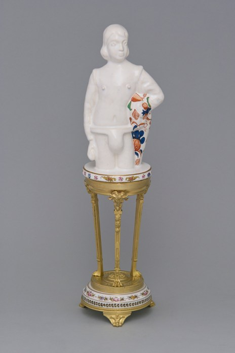 """Leopold Foulem, """"Boy with Cape on Empire Style Stand"""" 2012, ceramic, found object, decal, gold luster, 16.5 x 5 x 4.5"""". Courtesy of David Kaye Gallery"""
