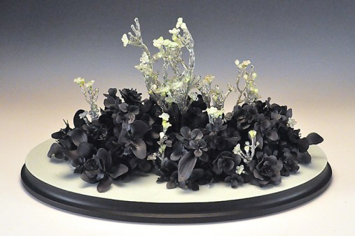 "Rain Harris, ""Florem Vernum"" 2013, wood, black clay, resin, silk flowers, 21 x 13 x 12""."