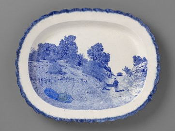 "Paul Scott, ""Scott's Cumbrian Blue(s), New American Scenery, The Uranium Series No. 1, Messa No: 1, Mine Road Cove, AZ"", 2019, in-glaze screen print (decal), on shell-edged pearlware platter c.1840 with uranium glass, 13.5 x 16.5 x 2""."