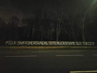"""May be an image of road and text that says """"MILK SNATCHERS!MEAL STEALERSISAME OLD TORIES! 1 1"""""""
